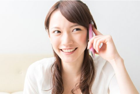 留学先で電話する女性